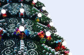 A fragment of a huge Christmas tree with many ornaments, gift boxes and luminous lamps. Photo of a decorated Christmas tree close-up with copy space