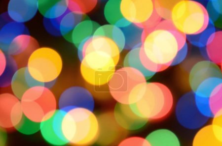 Blurred festive colorful lights over black useful as background. All main colors included. Red, yellow, green and blue