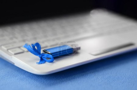 Brilliant blue usb flash memory card with a blue bow lies on a blanket of soft and furry light blue fleece fabric beside to a white laptop. Classic female gift design for a memory card