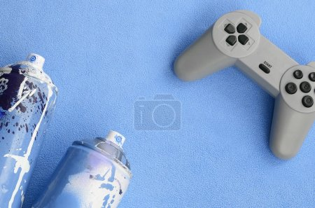 Teenagers and youth lifestyle concept. Joystick and two spray cans lies on the blanket of furry blue fleece fabric. Controllers for video games and paint cans on a plush fleece material background