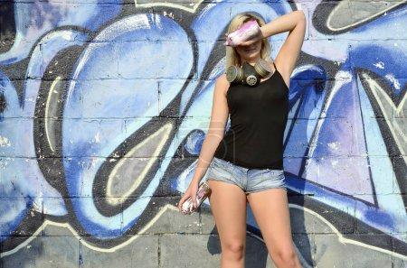 Photo pour Jeune et belle artiste de graffiti fille sexy souriant avec masque à gaz sur son cou se cachant les yeux avec un spray peuvent se tenant debout sur un fond de mur avec un motif de graffiti dans les tons bleus et violets - image libre de droit