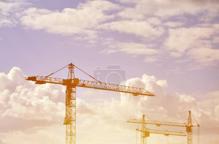 Tall and heavy construction crane towers against a blue sky in the evening sunset