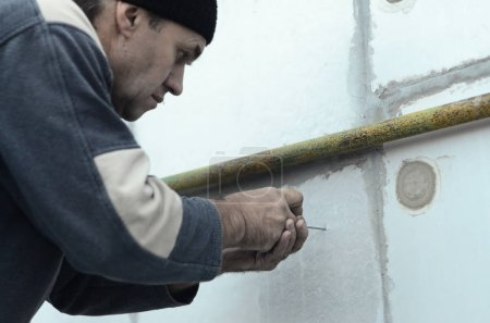 An elderly worker creates holes in the expanded polystyrene wall for the subsequent drilling and installation of an umbrella dowel. The process of fixing expanded polystyrene plates. Insulation work