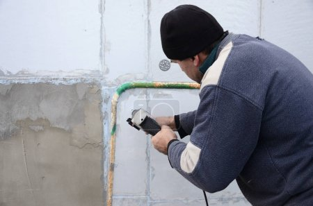 An elderly workman drills a hole in a styrofoam wall for the subsequent installation of a plastic reinforcing dowel. Creating holes in the wall with a drill. Warming of the building facade
