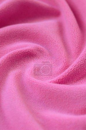 Photo pour La couverture de tissu polaire rose fourrure. Un fond de molleton doux rose clair avec beaucoup de plis en relief - image libre de droit
