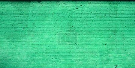 Photo pour La texture du mur de briques de nombreuses rangées de briques peintes en couleur verte - image libre de droit