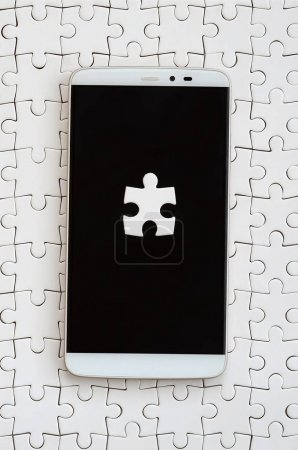 A modern big smartphone with several puzzle elements on the touch screen lies on a white jigsaw puzzle in an assembled state