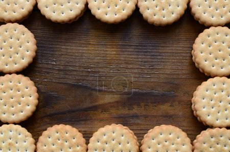 A frame of round cookie sandwich with coconut filling on a dark brown wooden surface. Unusual use of cookies as a frame. Image with copy space