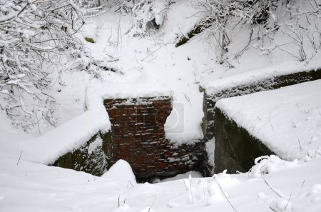 Underground bunker of old brick walls in winter after snowfall