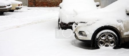 Fragment of the car under a layer of snow after a heavy snowfall. The body of the car is covered with white snow