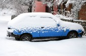 Photo of a car covered in a thick layer of snow. Consequences of heavy snowfall
