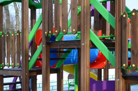 Fragment of a playground made of plastic and wood, painted in different colors