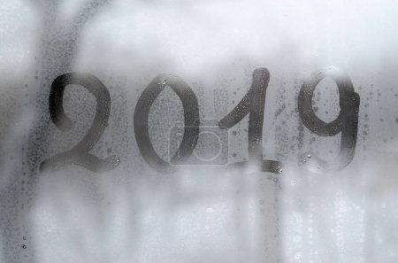 2019. The figures are written on the misted glass in winter