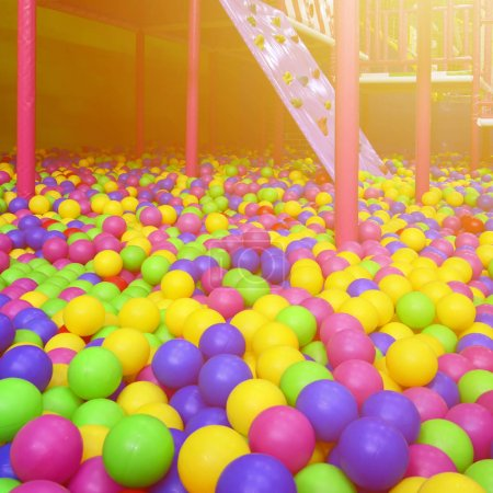 Many colorful plastic balls in a kids' ballpit at a playground