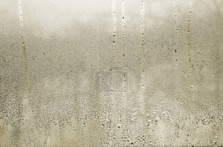 Photo for Texture of a drop of rain on a glass wet transparent background. Toned in yellow color - Royalty Free Image