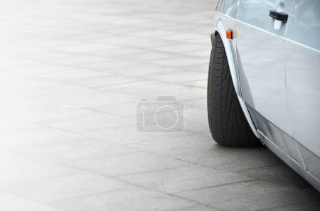 Diagonal view of a white glossy car that stands on a square of gray tiles