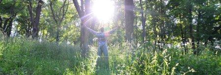 Photo pour Un jeune homme en costume de sport gris se réjouit du lever du soleil parmi les arbres de la forêt. Loisirs lors d'une course sportive en pleine forêt. Le délice d'une belle aube - image libre de droit