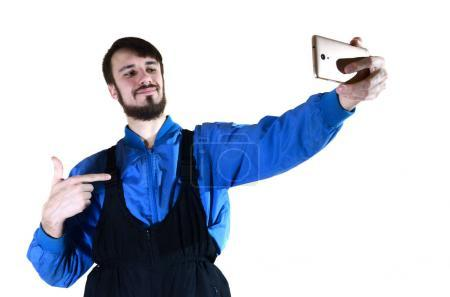 A young bearded guy in a work uniform makes a selfie on a modern smartphone, pointing to himself with his finger. A proud worker photographs himself. Isolated on white