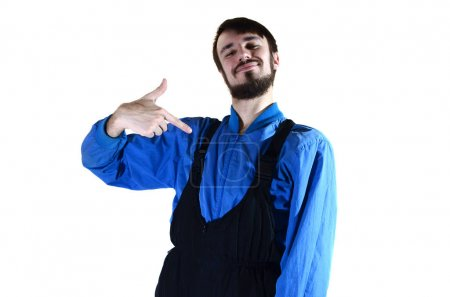 A young bearded guy in working uniform points to himself with his finger. A proud worker takes praise and encouragement to his person. Isolated on white