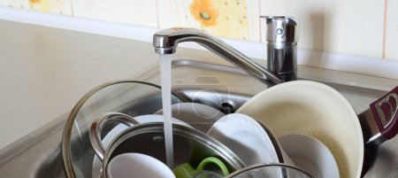 Dirty dishes and unwashed kitchen appliances lie in foam water under a tap from a kitchen faucet
