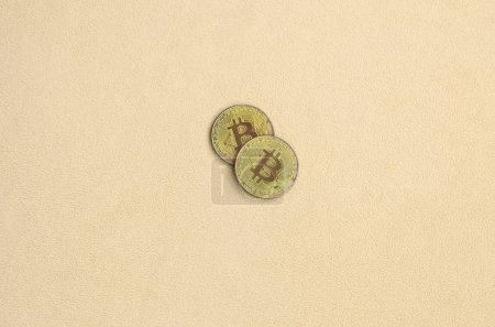 Photo pour Deux bitcoins dorés reposent sur une couverture faite de tissu polaire doux et moelleux orange clair. Visualisation physique de crypto monnaie virtuelle - image libre de droit