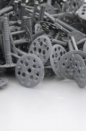 Background of many gray plastic dowels fastening for thermal insulation. A huge pile of plastic bolts with round holey hats lies on a gray foam polystyrene plate