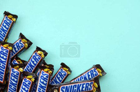 Photo for KHARKOV, UKRAINE - OCTOBER 2, 2019: Many Snickers chocolate bars lies on pastel blue paper. Snickers bars are produced by Mars Incorporated. Snickers was created by Franklin Clarence Mars in 1930 - Royalty Free Image