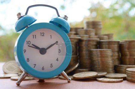 Photo pour Le réveil bleu sur une grande quantité de vieilles piles de pièces ukrainiennes de 1 hryvnia se referme sur un fond vert flou d'arbres. Le concept de planification financière et de gestion du temps d'affaires - image libre de droit