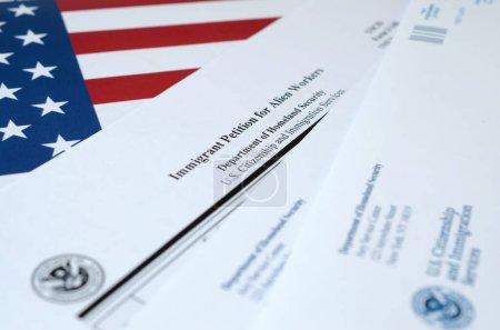 Photo pour I-140 Immigrant pétition pour les travailleurs étrangers formulaire vierge se trouve sur le drapeau des États-Unis avec une enveloppe du ministère de la Sécurité intérieure gros plan - image libre de droit