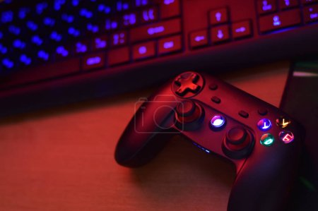 Photo for Modern gamepad lies with pc keyboard on table in dark playroom scene close up. Gameplay streaming and video game walkthroughts concept - Royalty Free Image