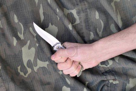 Photo pour Poignée avec petit couteau sur fond de tissu de camouflage. Le concept de l'utilisation d'un couteau dans les tactiques de mêlée entre militaires - image libre de droit