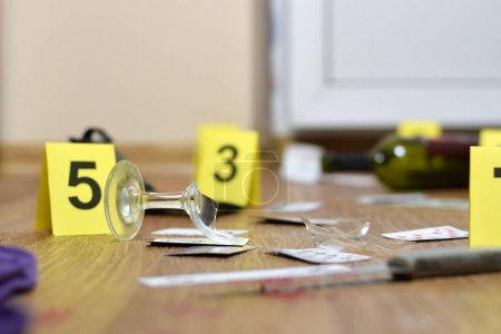 Photo for Crime scene investigation - numbering of evidences after the murder in the apartment. Broken glass of wine, knife and bottle as evidence close up - Royalty Free Image