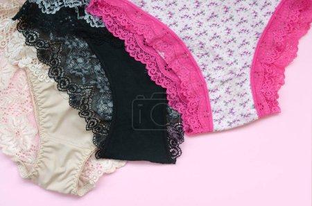Photo pour Sous-vêtements féminins blancs, noirs et roses avec dentelle sur fond rose de près avec espace de copie. Publicité pour le magasin de sous-vêtements féminins beaux et confortables - image libre de droit
