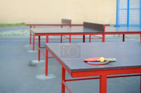 Photo pour Raquettes et ballon près de la table de pong Ping dans la cour de sport en plein air. Concept de sport actif et d'entraînement physique - image libre de droit