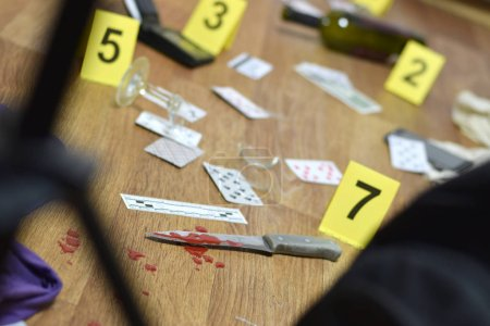 Photo for Crime scene investigation - numbering of evidences after the murder in the apartment. A lot of playing cards, wallet and bottle of wine as evidence close up - Royalty Free Image