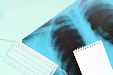 Photo for Respiratory mask and empty notepad page on x-ray of human lungs, top view. Coronavirus Covid-19 pneumonia concept. - Royalty Free Image