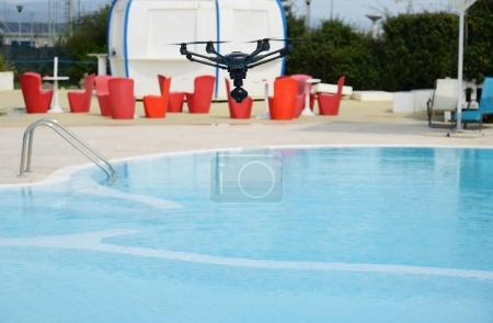 Photo for Drone hovering over swimming pool - Royalty Free Image