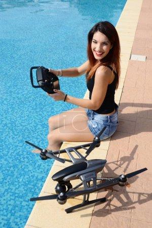 Photo pour Fille voler drone avec télécommande près de la piscine - image libre de droit