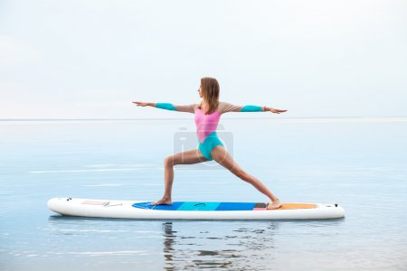 Woman doing yoga on sup board with paddle