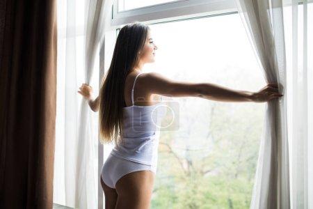 Photo pour Belle femme se réveilla et debout devant la fenêtre. Jeune fille ouvre rideaux et sunrise de la réunion - image libre de droit