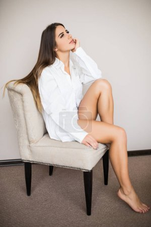 woman in man shirt sitting on chair