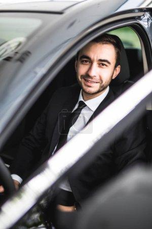Photo pour Heureux conducteur souriant dans la portière ouverte - image libre de droit