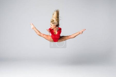 Young beauty blonde slim woman in red body jumping and doing gymnastic exercises on white background