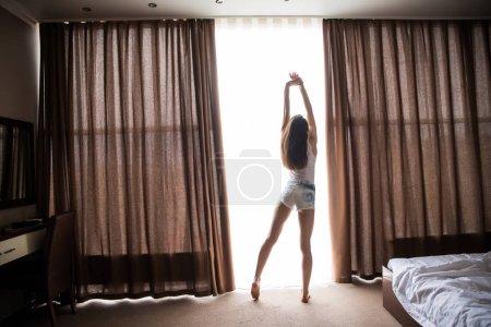 Photo pour Femme est réveillée et debout devant la fenêtre. La fille ouvre les rideaux et rencontre le lever du soleil - image libre de droit