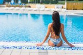 Back view of brunette woman in swimsuit and hat sitting near the pool. Summer vocation
