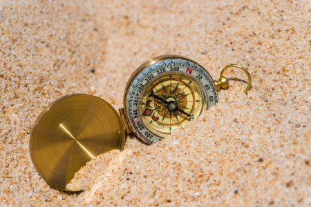 Compass in the gold sand on the beach. Summer time