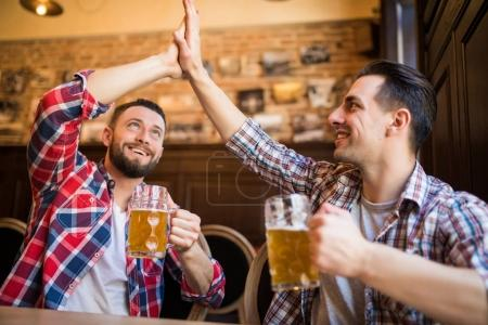 Happy young bearded man laughing high fiving his friend while having beer at the pub together