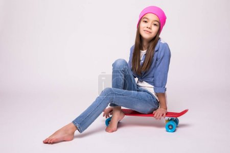 Happy little girl in rose hat skateboarder sitting on longboard, isolated on white background
