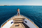 Man on a yacht. Beautiful view from a bow of a yacht at seaward. Sailing. Luxury yachts. Summer vacation and voyage concept