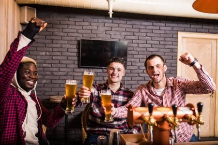 Group of male friends watching football match in pub win shout scream